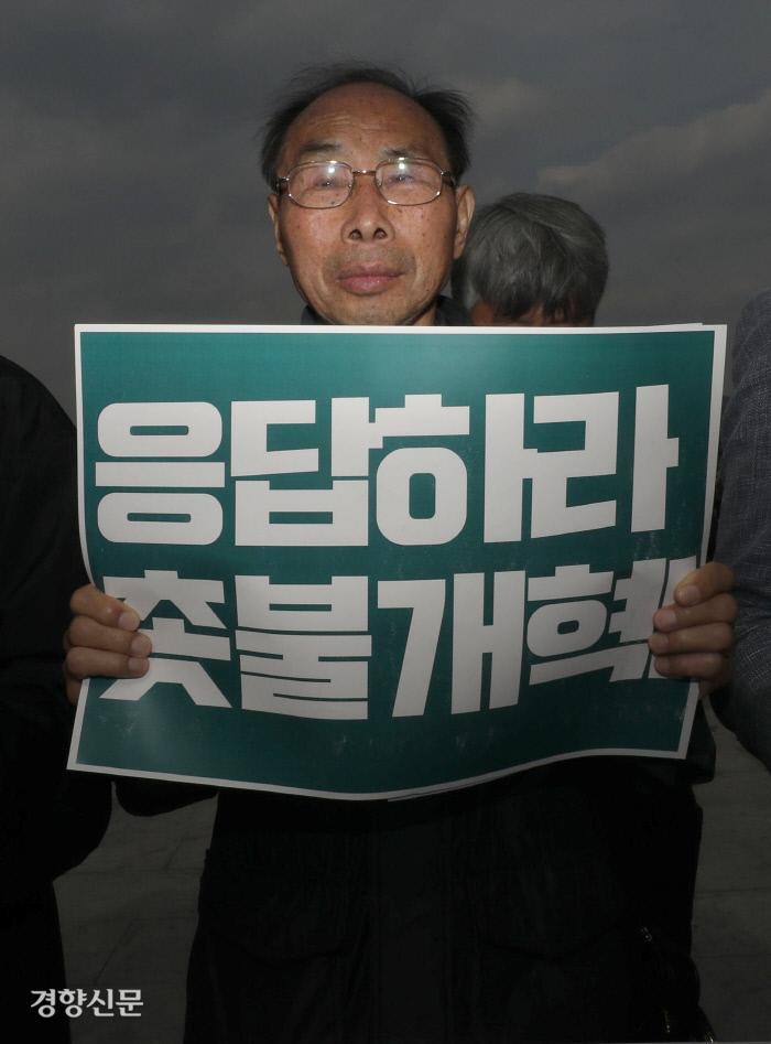 권오헌 양심수후원회 명예회장 등 시민사회단체 관계자들이 28일 오후 서울 광화문광장 '응답하라 적폐청산! 촛불대개혁!' 기자회견에서 지속적인 개혁을 촉구하는 손팻말을 들고 있다.  권도현 기자 lightroad@kyunghyang.com