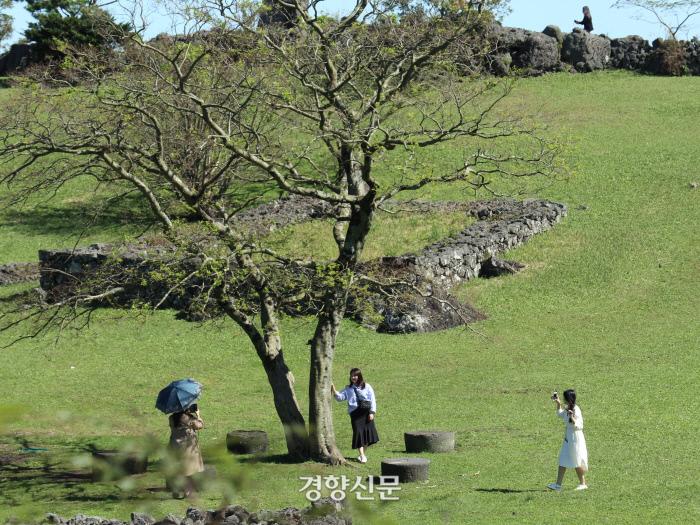 천연기념물로 지정된 산굼부리의 분화구 옆 언덕에서 기념사진을 찍은 관광객들