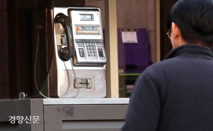 한 시민이 전용카드를 사용하는 공중전화를 바라보고 있다. /김기남 기자