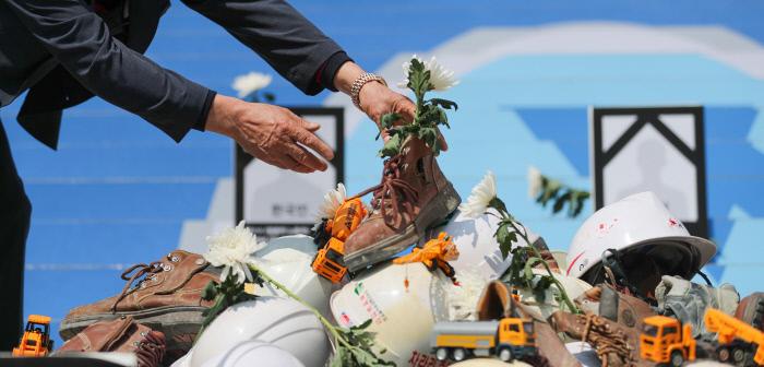지난 4월 산재사망대책마련공동캠페인단이 연 '2020 최악의 살인기업 선정식' 기자회견에서 한 산재피해자 유족이 산재사망자들을 기리는 물품 위에 국화꽃을 놓고 있다. 이준헌 기자 ifwedont@kyunghyang.com