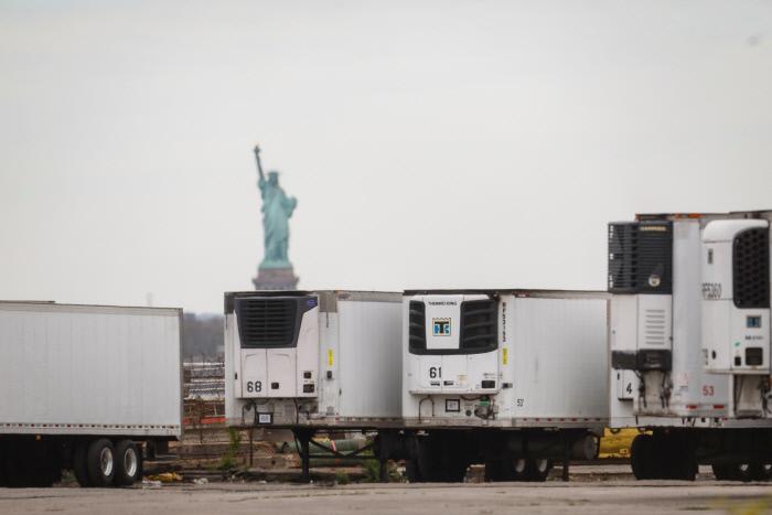 코로나19로 사망자가 폭증한 미국 뉴욕에서 지난 5월 브루클린의 임시 영안시설로 시신들을 운반하는 냉동 트럭들이 자유의 여신상이 보이는 곳에 정차해 있다. 로이터연합뉴스