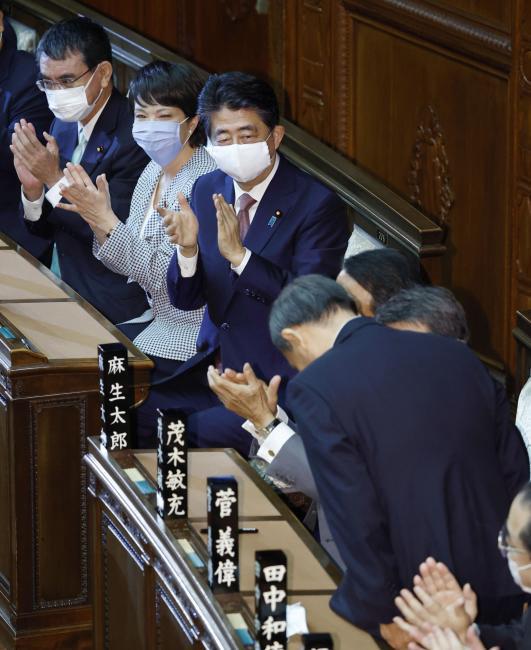 지난 16일 제99대 총리로 선출된 스가 요시히데 자민당 총재가 아베 신조 전 총리(왼쪽에서 세번째)를 향해 고개 숙여 인사하고 있다. 도쿄|교도연합뉴스