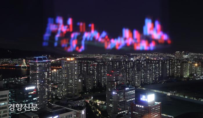 지난달 19일 서울 송파구 롯데월드타워 31층 전망대 유리창 바깥의 아파트단지 위로 태블릿PC에 띄운 주식 차트가 비춰져 있다. 권도현 기자
