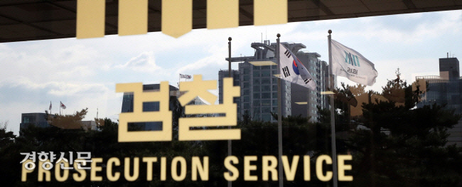 پرچم دادستانی و Taegeukgi بر روی دیوار شیشه ای دفتر دادستان مرکز سئول در Seocho-dong ، سئول منعکس شده است.  عکس روزنامه کیونگ یانگ
