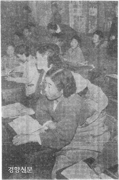 یک خانم خانه دار در حال نوشتن کتاب نوشتن با نوزادی به پشت در مدرسه ای در Seongdong-gu ، سئول در سال 1961. عکس روزنامه Kyunghyang.