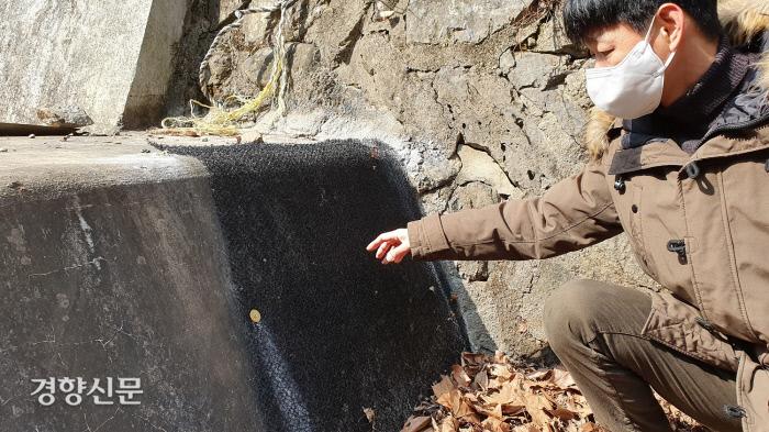 지난 10일 이경호 대전환경운동연합 사무처장이 대전 동구 식장산 세천저수지 아래 보에 설치된 개구리사다리를 손으로 가리키고 있다. 윤희일 선임기자