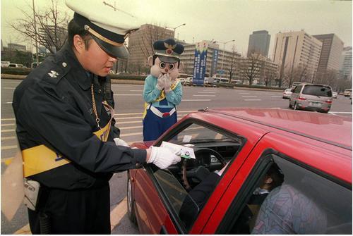 در تاریخ 2 آوریل 2001 ، هنگامی که سرکوب شدید علیه افرادی که کمربند ایمنی به سر ندارند آغاز شد ، یک افسر پلیس با صدور برچسب ، رانندگانی را که از کمربند ایمنی استفاده نکردند در مقابل ساختمان دولت مرکزی در Sejongro ، سئول مجازات کرد.  عکس روزنامه کیونگ یانگ.