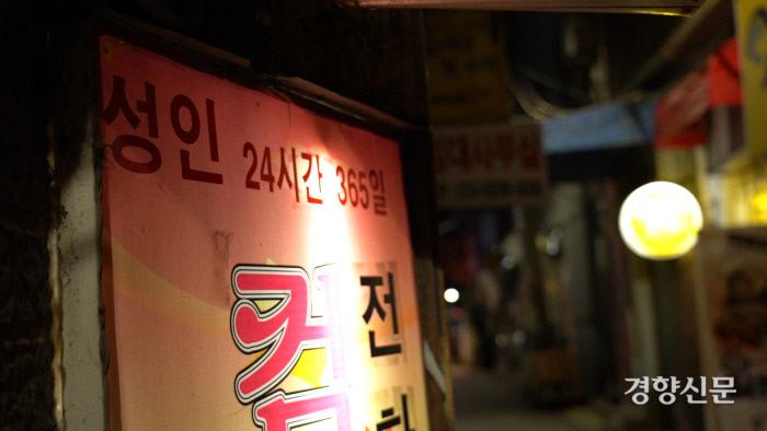 نشانه ای از تجارت مشابه با تن فروشی خیابانی در Bukchang-dong ، Jung-gu ، سئول.  مردانی که اقدام به خرید رابطه جنسی می کنند بسته به نحوه پرداخت در لحظه نحوه فروش رابطه جنسی را تغییر می دهند و سعی می کنند نیازهای خود را برآورده کنند.  P. D. Choi Eugene