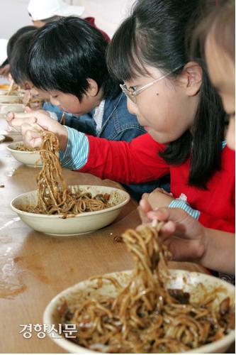 کودکان شرکت کننده در مسابقه فست فود جاژانگمیون که به مناسبت صدمین سالگرد تولد جاجانگمیون در منطقه اینچئون چین در 7 اکتبر 2005 برگزار شد ، جاجانگمیون را می خورند.  عکس روزنامه کیونگ یانگ.