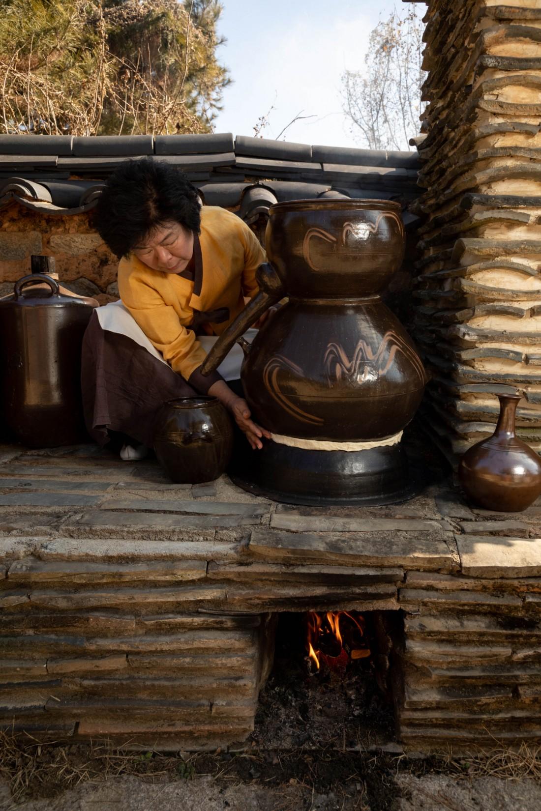 박 명인이 솔송주를 가열해 증류주인 담솔을 내리면서 증기가 새어나가지 않도록 밀가루 반죽으로 소줏고리의 이음매를 막고있다.  우철훈 선임기자 photowoo@kyunghyang.com