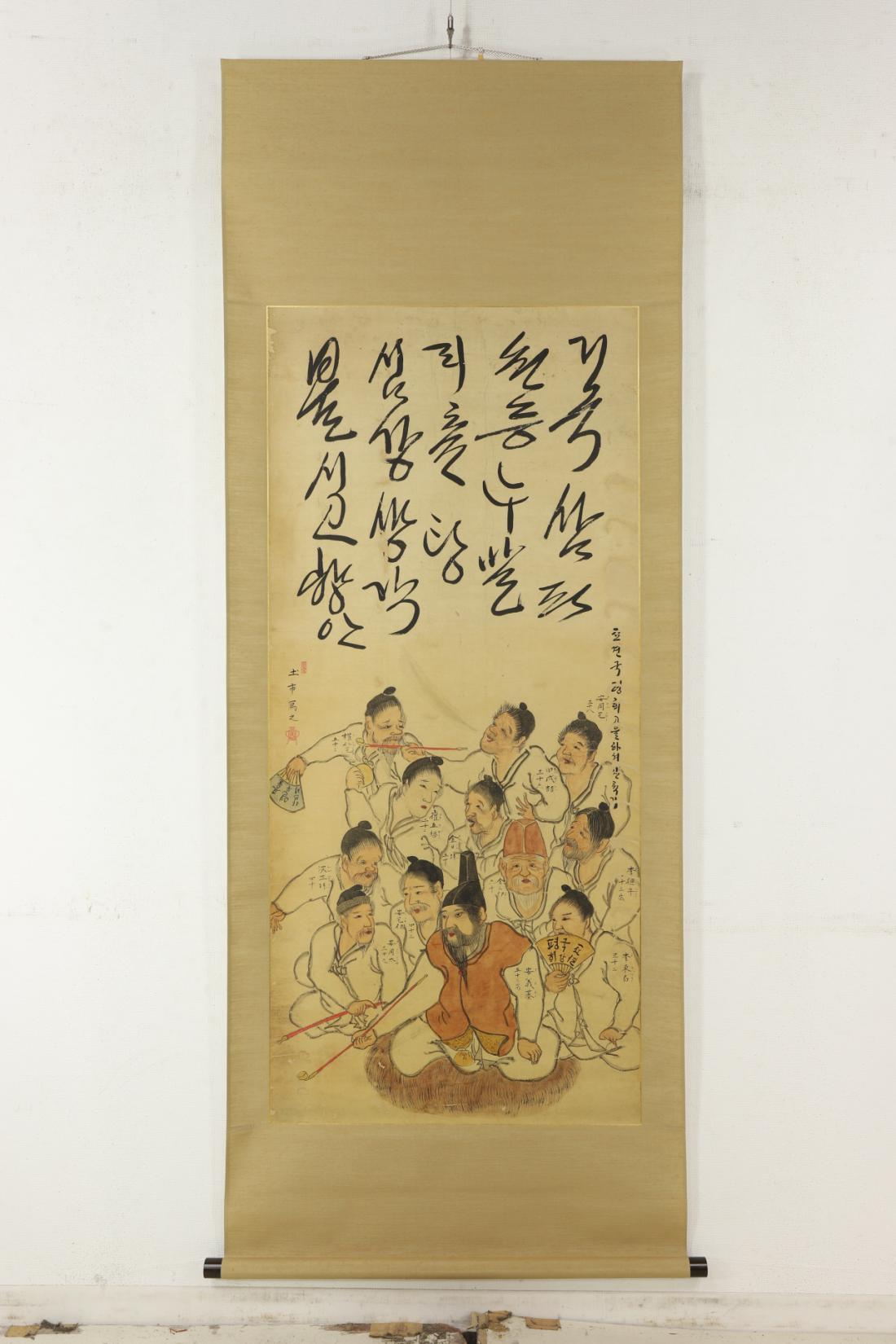 1819년 1월 강원 평해(현 경북 울진)에서 출항한 선박이 일본 돗토리번에 표착해서 9개월만에 귀환했다. 이 그림은 돗토리번에 표착한 조선인 12명을 그린 초상화이다. 담뱃대를 물고 있는 안의기(53)를 중심으로 권인택(52), 김삼이(60), 안택이(43), 전성철(32), 김일손(50), 안용태(39), 심정손(40), 안용택(38), 이동백(32), 최오복(22), 이덕수(43) 등의 이름과 나이가 쓰여져 있다. 피부색과 마마를 앓은 자국, 옷주름, 담뱃대, 부채 등 소품의 특징묘사가 뛰어나다. 그림 윗부분에 대문짝만 하게 흘림체로 쓴 한글글씨가 있다. |서예박물관 제공