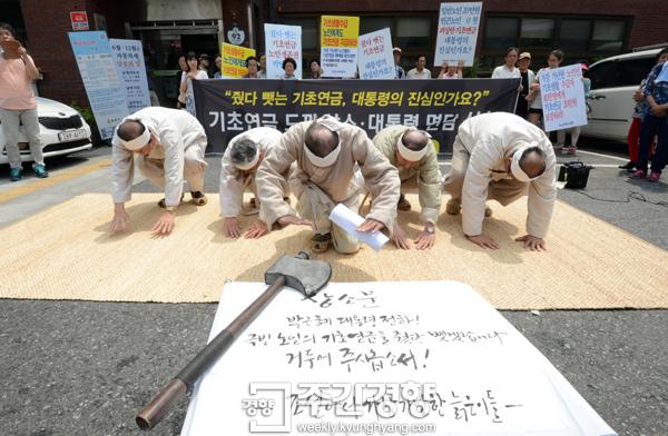 2014년 7월 노년유니온 등 단체들이 서울 청운효자동 주민센터 앞에서 '줬다 뺏는 기초연금'을 규탄하는 퍼포먼스를 하고 있다./김정근 기자