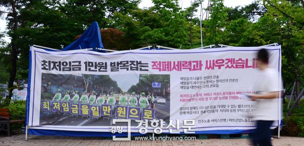 7월 16일 서울 여의도 국회 정문 앞에 설치된 최저임금 1만원을 요구하는 민주노총 서비스연맹의 대형 플래카드 앞으로 시민이 지나가고 있다. 김창길 기자