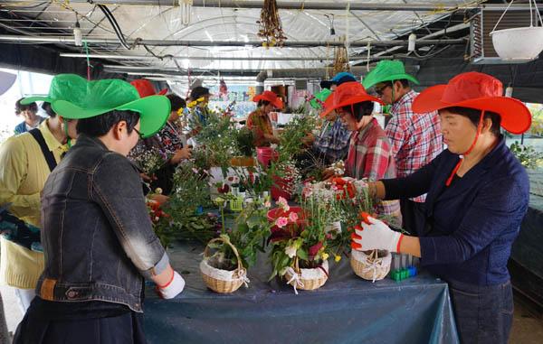 전북 고창의 치유농업 프로그램인 '쉼드림'에 참가한 사람들이 수확한 꽃으로 장식물을 만드는 활동을 하고 있다. / 농촌진흥청 제공