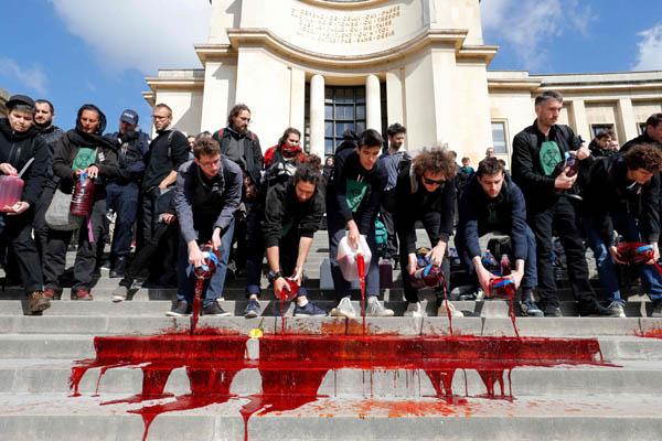 기후변화 방지 운동단체 '멸종저항' 소속 활동가들이 5월 12일(현지시간) 프랑스 파리 도심 트로카데로 광장에서 생물다양성 감소에 대한 경각심을 일으키기 위해 광장 계단에 '가짜 피'를 흘려보내며 시위를 벌이고 있다. / AFP|연합뉴스