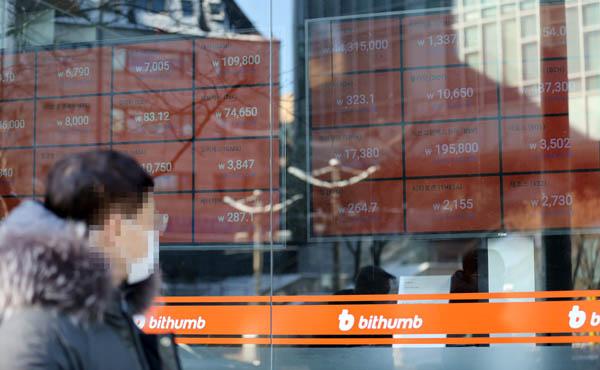 한 시민이 서울 빗썸 강남센터 암호화폐 시세 현황표 앞을 지나가고 있다. / 연합뉴스
