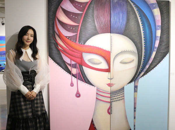 배우이자 작가인 김혜진이 자신의 작품을 배경으로 포즈를 취하고 있다.