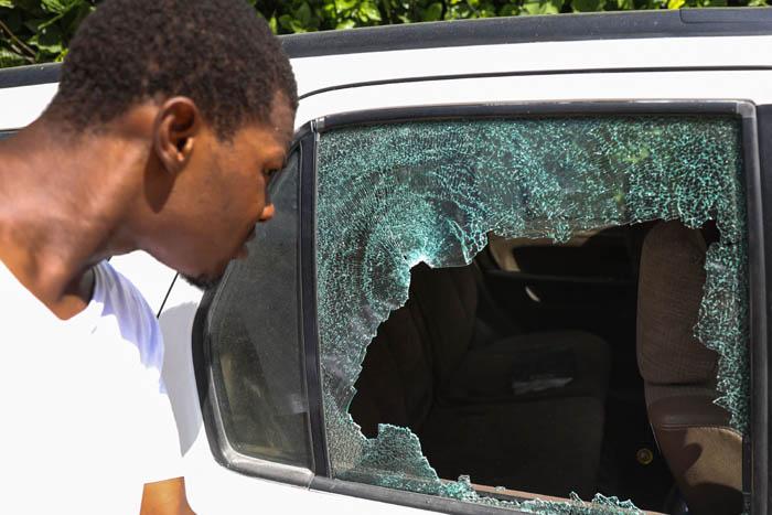한 남성이 조브넬 모이즈 아이티 대통령의 사저 밖에서 7일(현지시간) 총에 맞아 창문이 깨진 자동차를 들여다보고 있다. 포르토프랭스 | AFP연합뉴스
