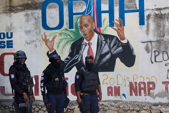 <b>누가 대통령을 쐈나</b> 무장 괴한에게 살해당한 조브넬 모이즈 아이티 대통령의 자택 주위에서 7일(현지시간) 경찰이 순찰을 돌고 있다. 경찰의 뒤에 모이즈 대통령이 그려진 벽화가 보인다. 포르토프랭스 | AP연합뉴스