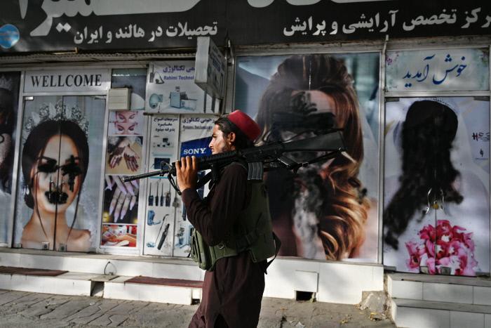 8월 18일(현지시간) 탈레반 조직원이 검은색 스프레이로 가려진 미용숍 외벽의 여성 사진을 지나가고 있다. 탈레반이 아프가니스탄을 장악하면서 여성 인권이 후퇴할 수 있다는 우려가 커지고 있는 가운데 최근 탈레반이 부르카를 입지 않은 여성을 총살했다는 소식이 알려졌다.   AFP연합뉴스