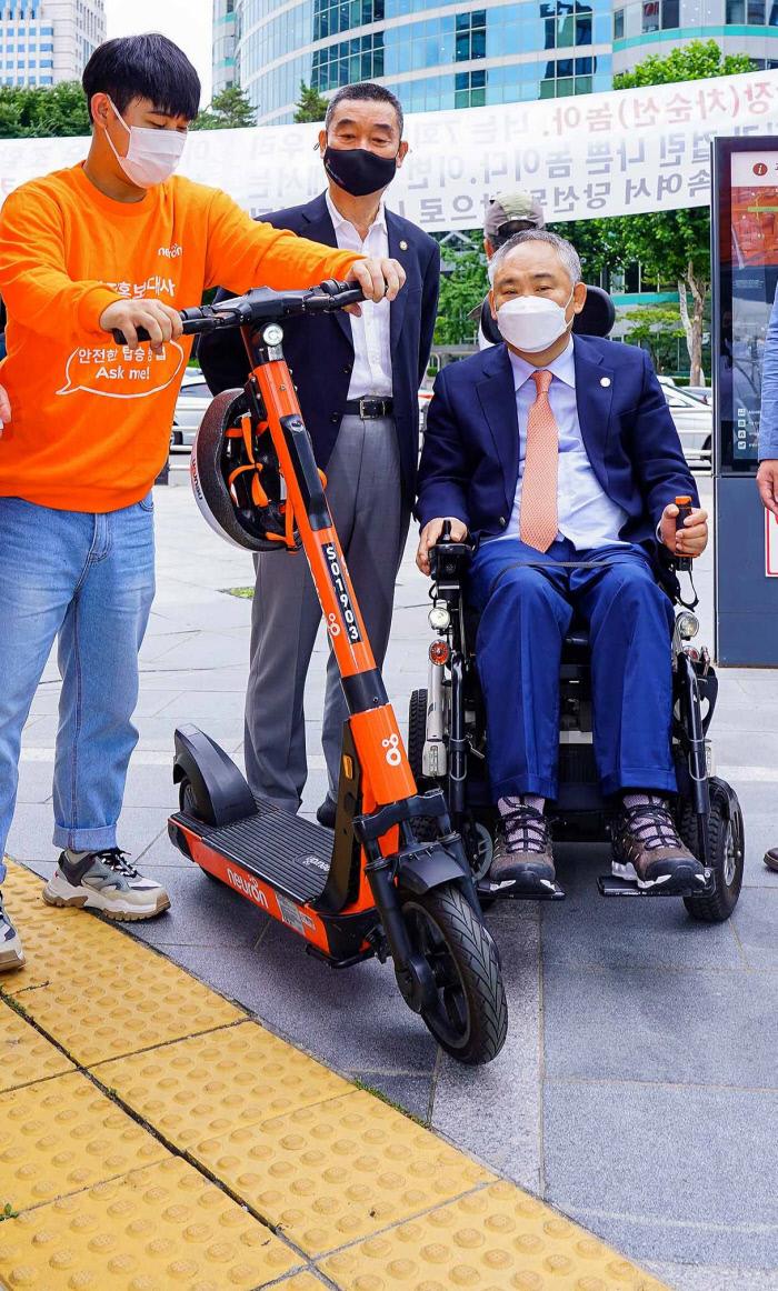 지난  6일 오후 서울 강남 삼성역 앞에서 뉴런모빌리티, 한국교통장애인협회, 안전생활실천시민연합 관계자들이 점자블록 위에서의 전동킥보드 주차 문제 등에 대한 점검을 실시하고 있다. 뉴런보빌리티 제공